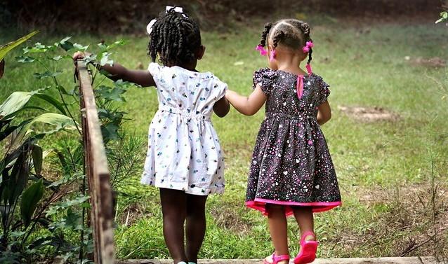 Two little girls holding hands - characteristics of a true friend