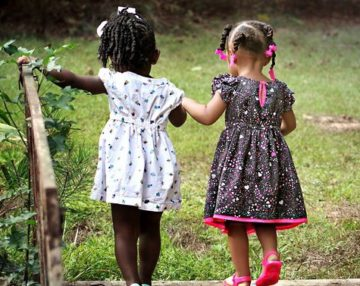 Two little girls holding hands - characteristics of a true friend
